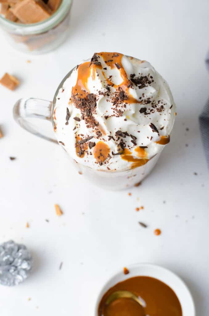 Overhead view of a mug of cocoa topped with whipped cream, caramel, and chocolate shavings.
