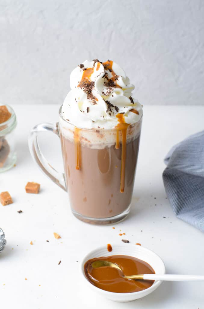 A mug of salted caramel hot chocolate, topped with whipped cream and dripping with caramel.