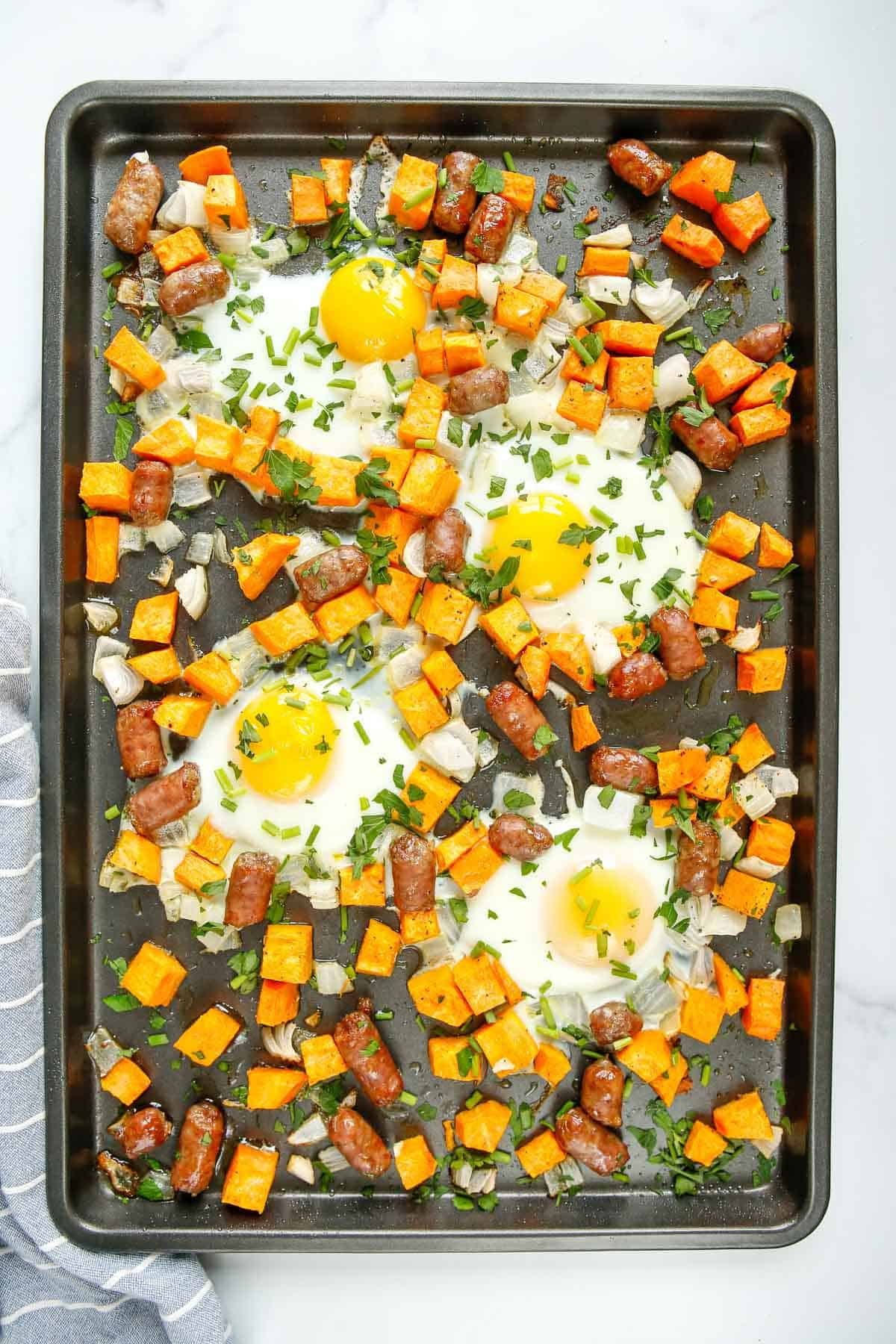Overhead view of a sheet pan full of breakfast food including eggs.