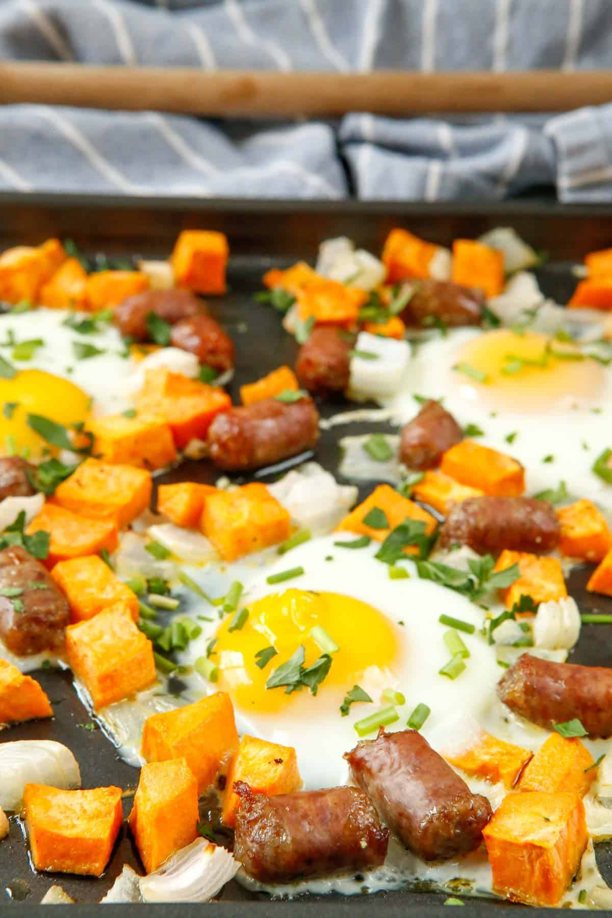 Eggs, sausage, and sweet potatoes on a sheet pan.