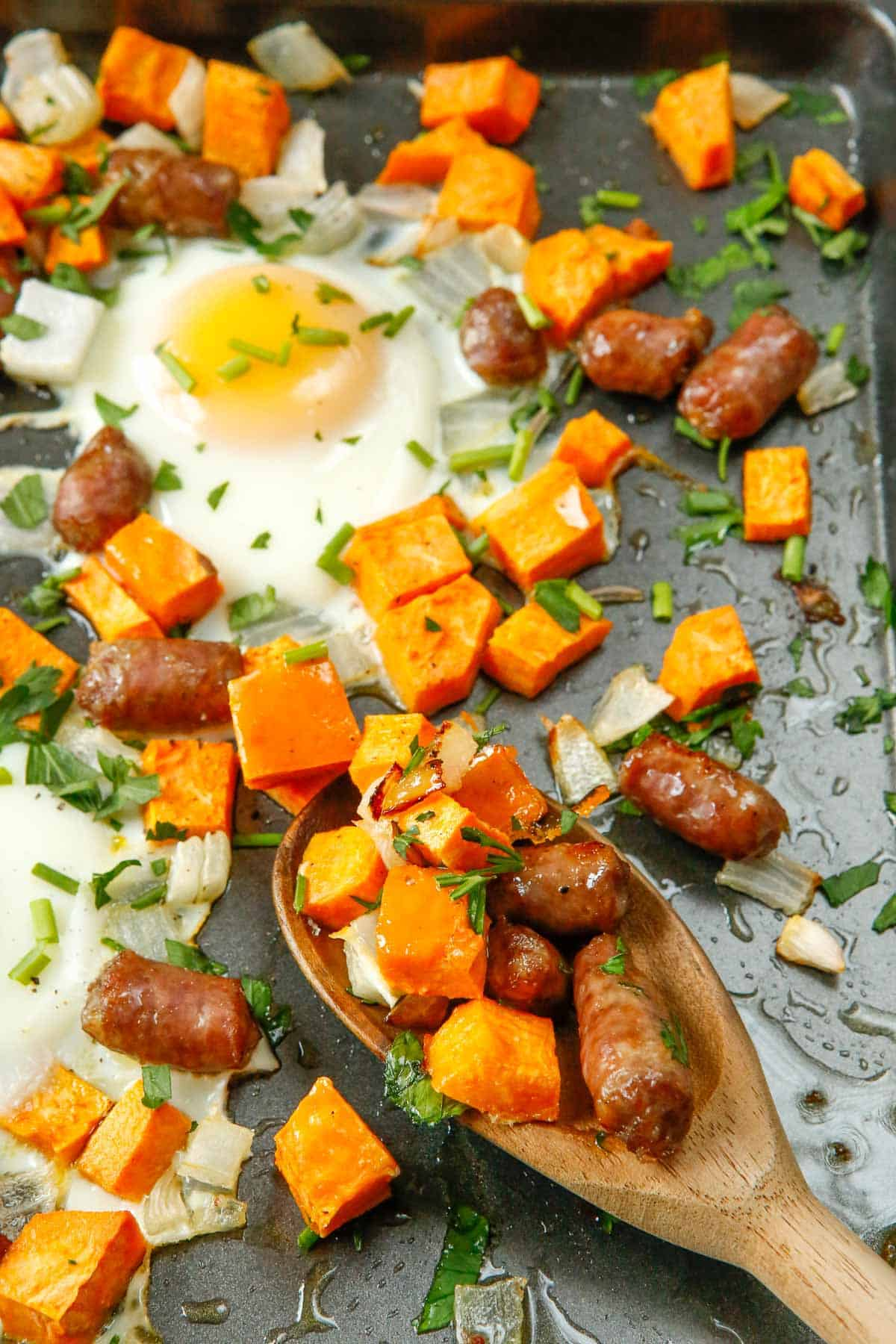 Breakfast hash being scooped up on a wooden spoon.