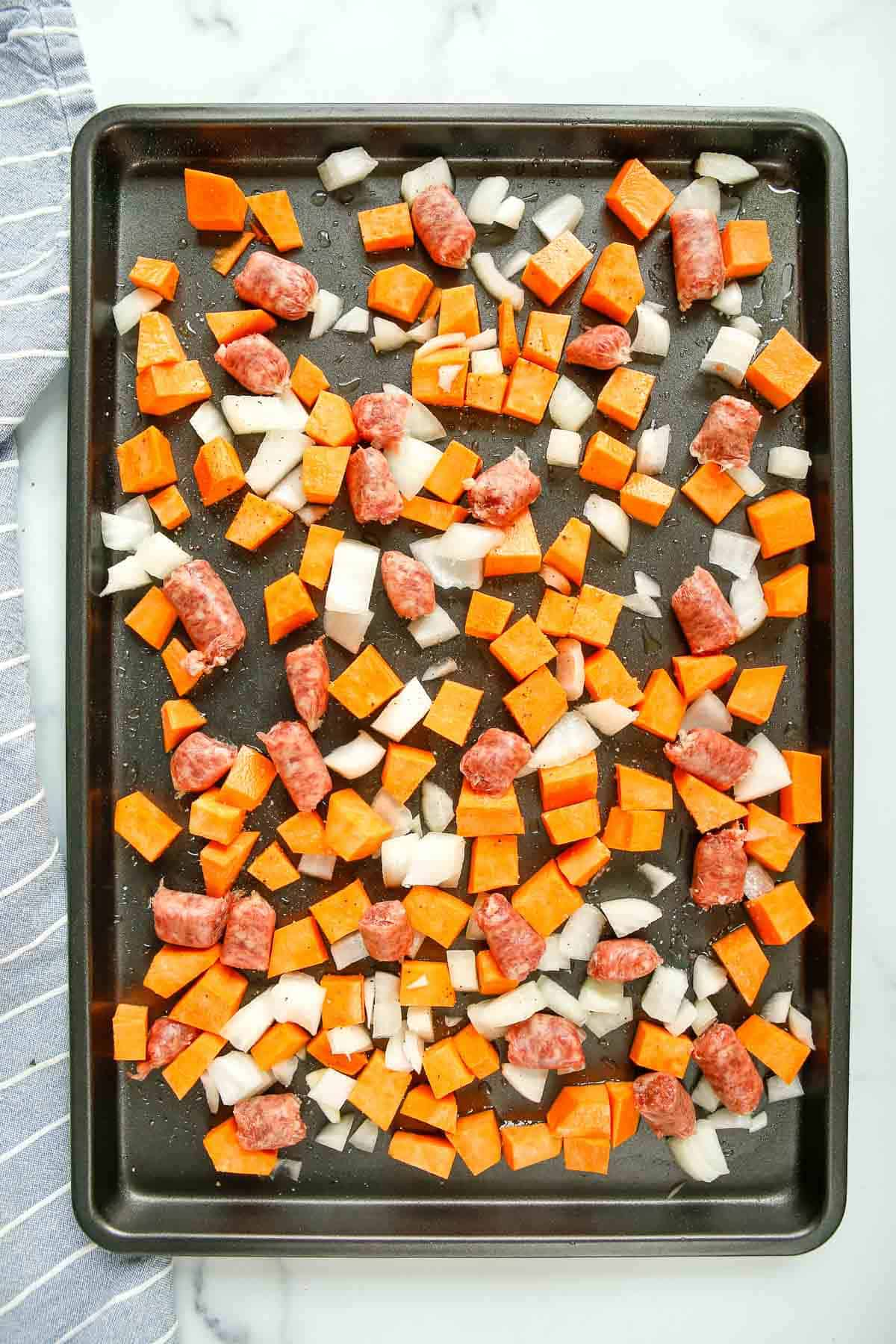 Sweet potatoes, onion, and uncooked sausage on a sheet pan.