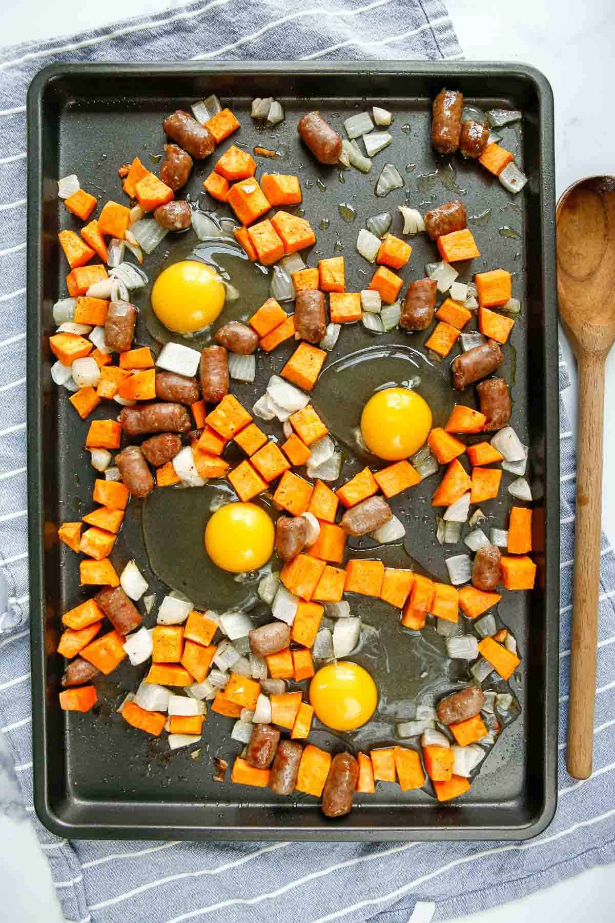 Overhead view of four uncooked eggs on a sheet pan with sweet potatoes and sausage.