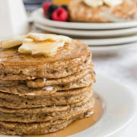 Stack of zucchini bread pancakes with butter and syrup.