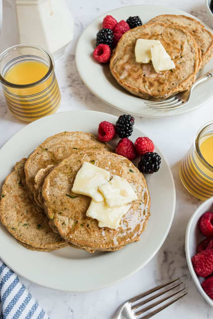 Overhead view of pancakes on plates, topped with butter and served with fresh berries.