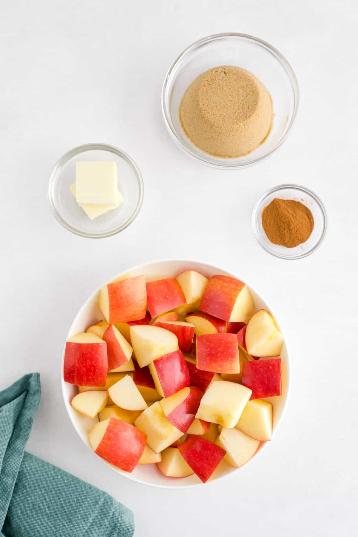 Four bowls filled with ingredients: diced apples, butter, brown sugar, and cinnamon.