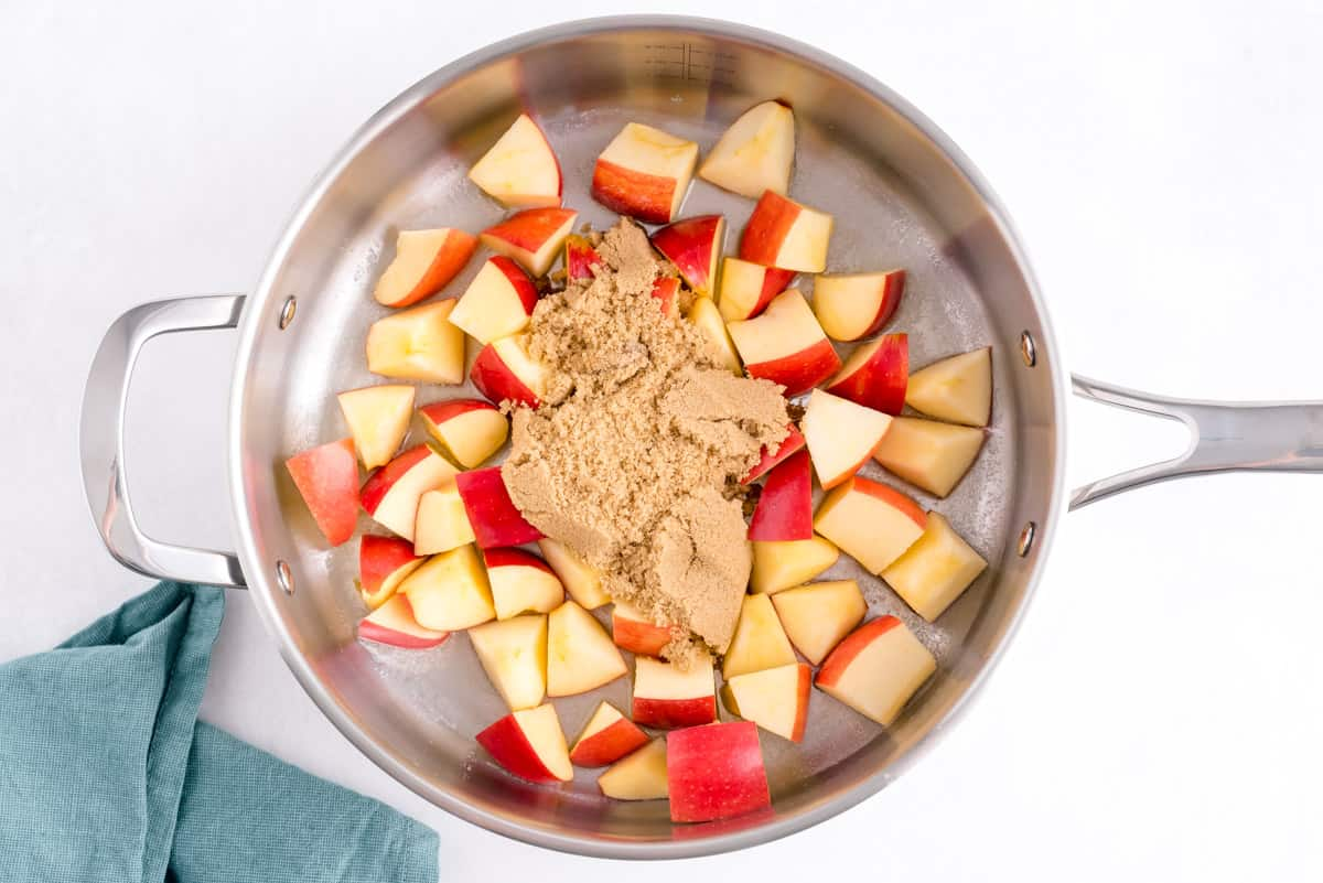 Uncooked apples and brown sugar in a pan.