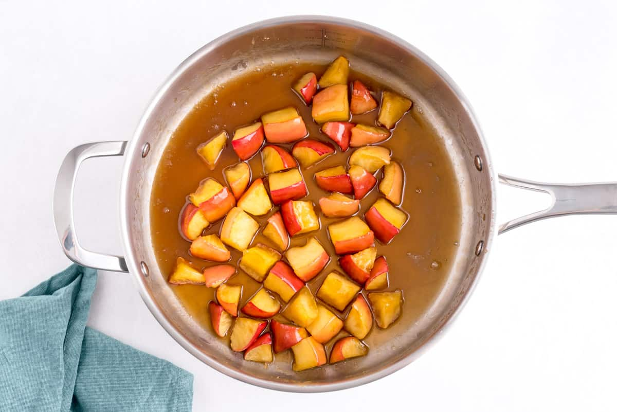 Cooked apples in a brown sugar sauce in a stainless steel skillet.
