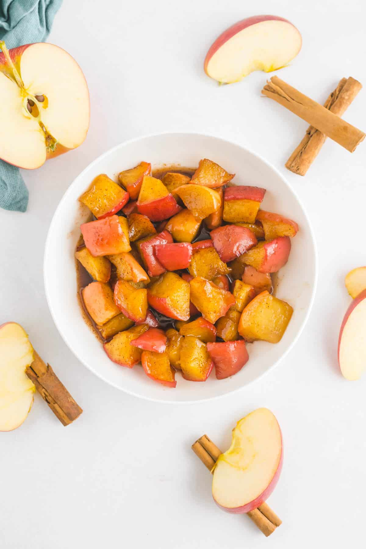 Apple compote in a white bowl, surrounded by apples and cinnamon sticks.