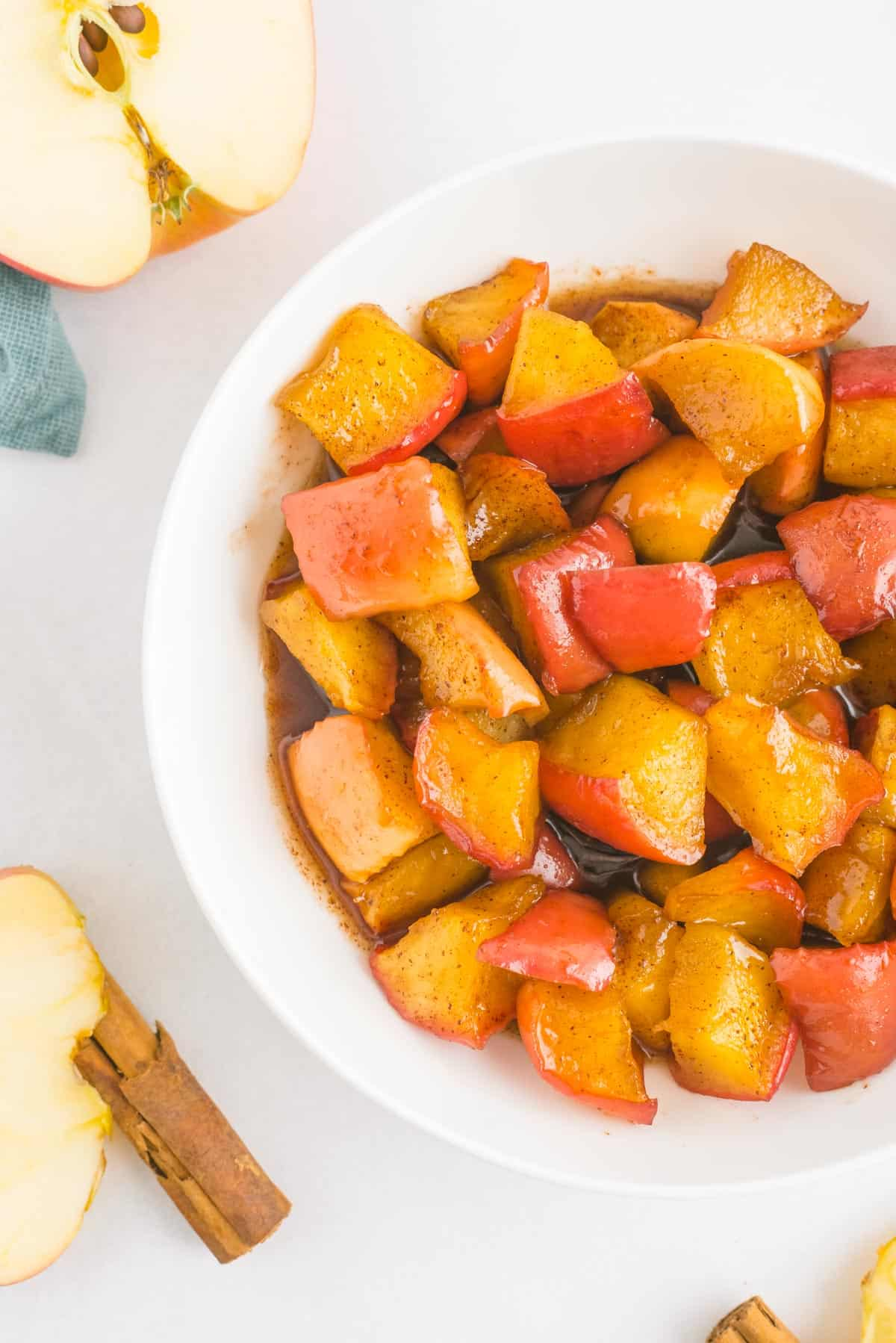 Cinnamon apple compote in a white bowl, with apple halves and cinnamon sticks also in the photo.