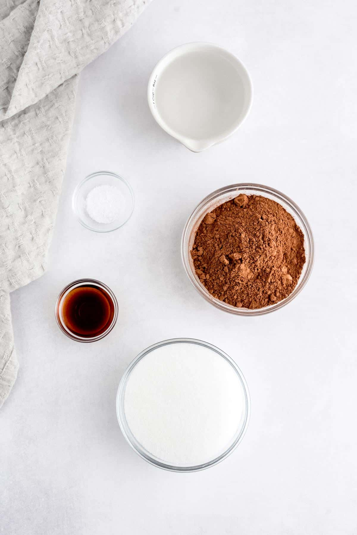 Five small bowls of ingredients: cocoa powder, sugar, vanilla, water, and salt.