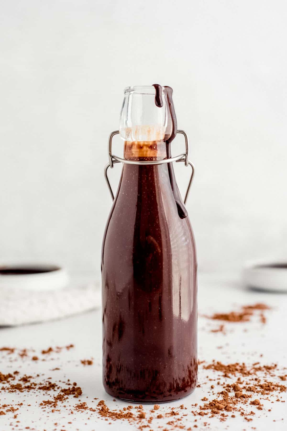 Homemade chocolate syrup in a clear glass bottle.