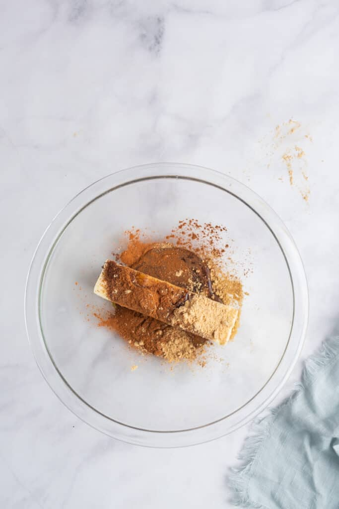All ingredients for a spiced gingerbread compound butter in a glass mixing bowl on a white marble background.
