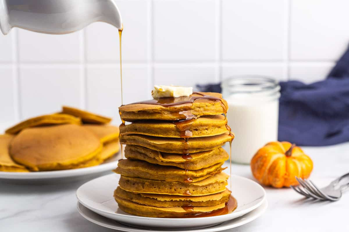 Pumpkin pancakes being drizzled with maple syrup.