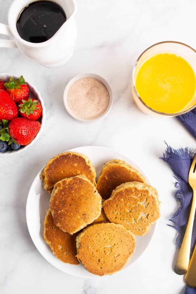 Pancakes on a plate with berries and orange juice nearby.