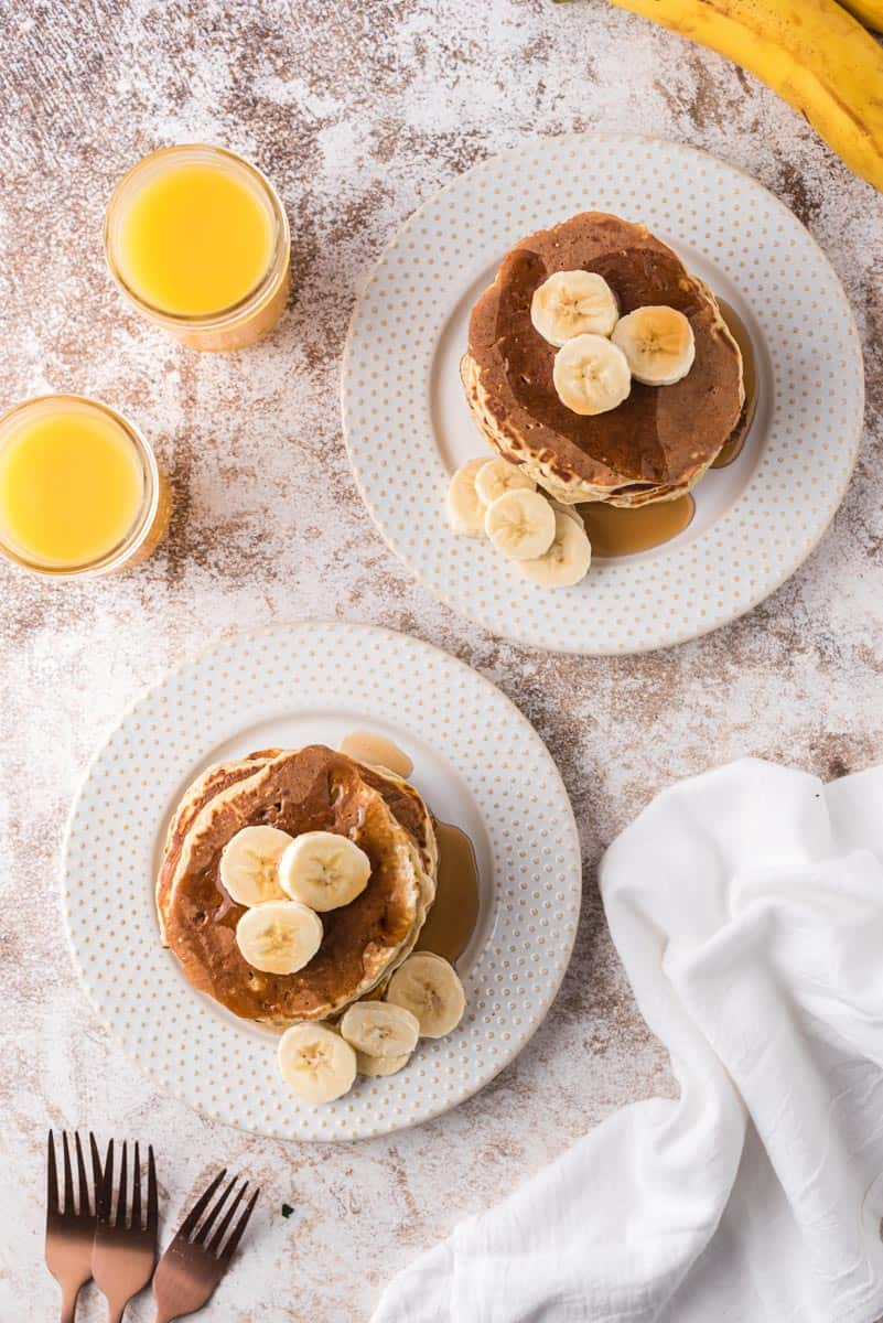 Overhead view of stacks of pancakes topped with bananas.