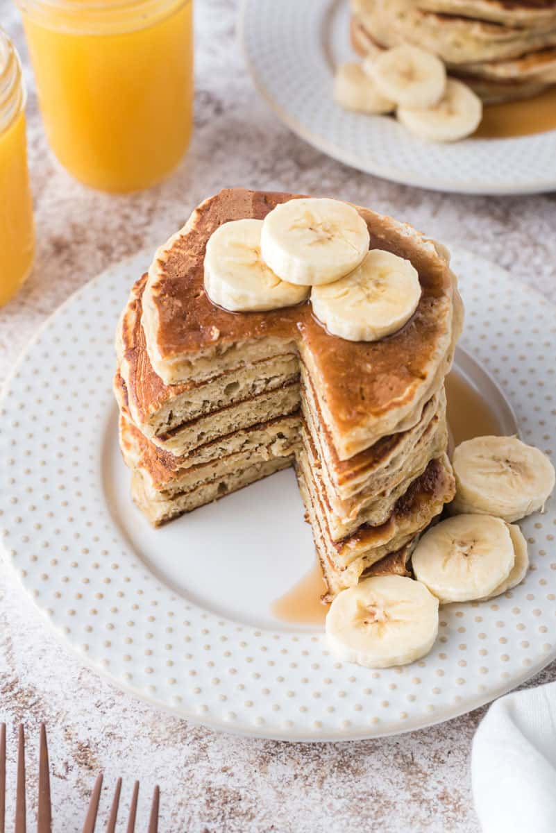 Stack of pancakes topped with banana slices, with a wedge cut out of the pancakes.