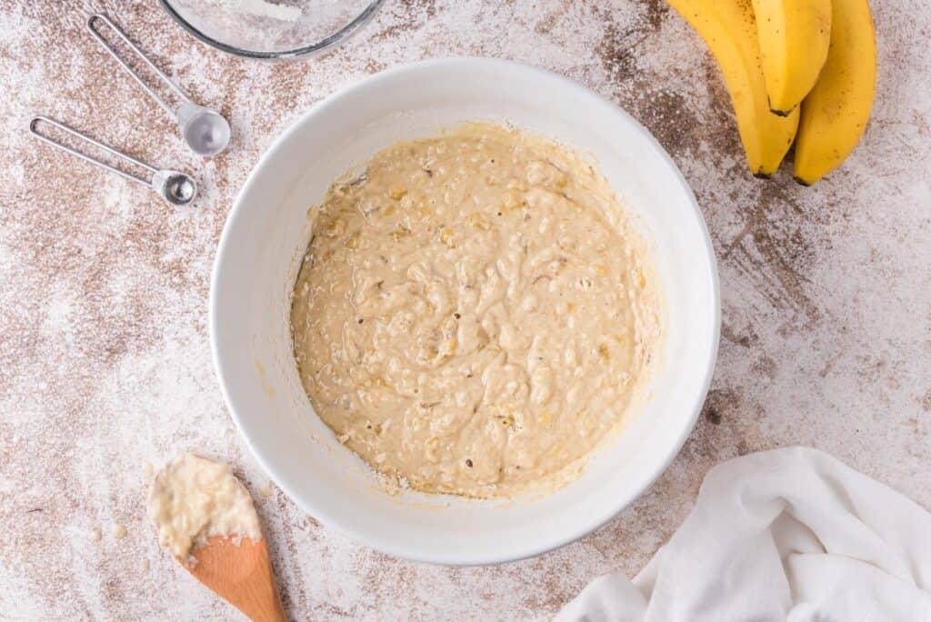 Banana pancake batter in a white bowl