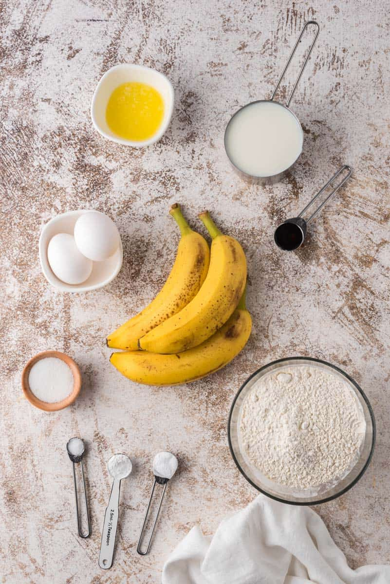 Ingredients on a brown and white surface: flours, sugars, ripe bananas, eggs, oil, vanilla extract.