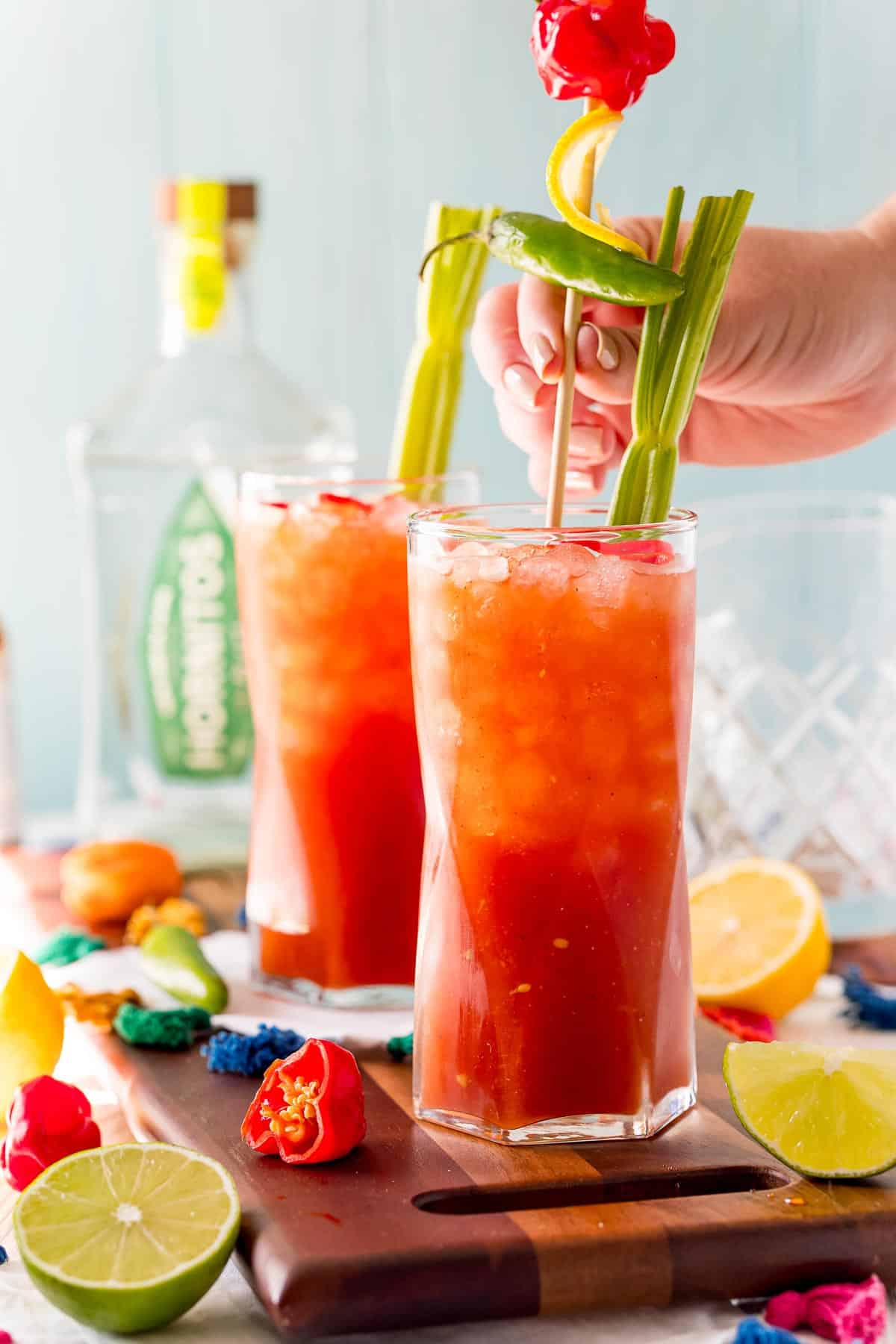 Garnishes being added to a bloody mary style drink.
