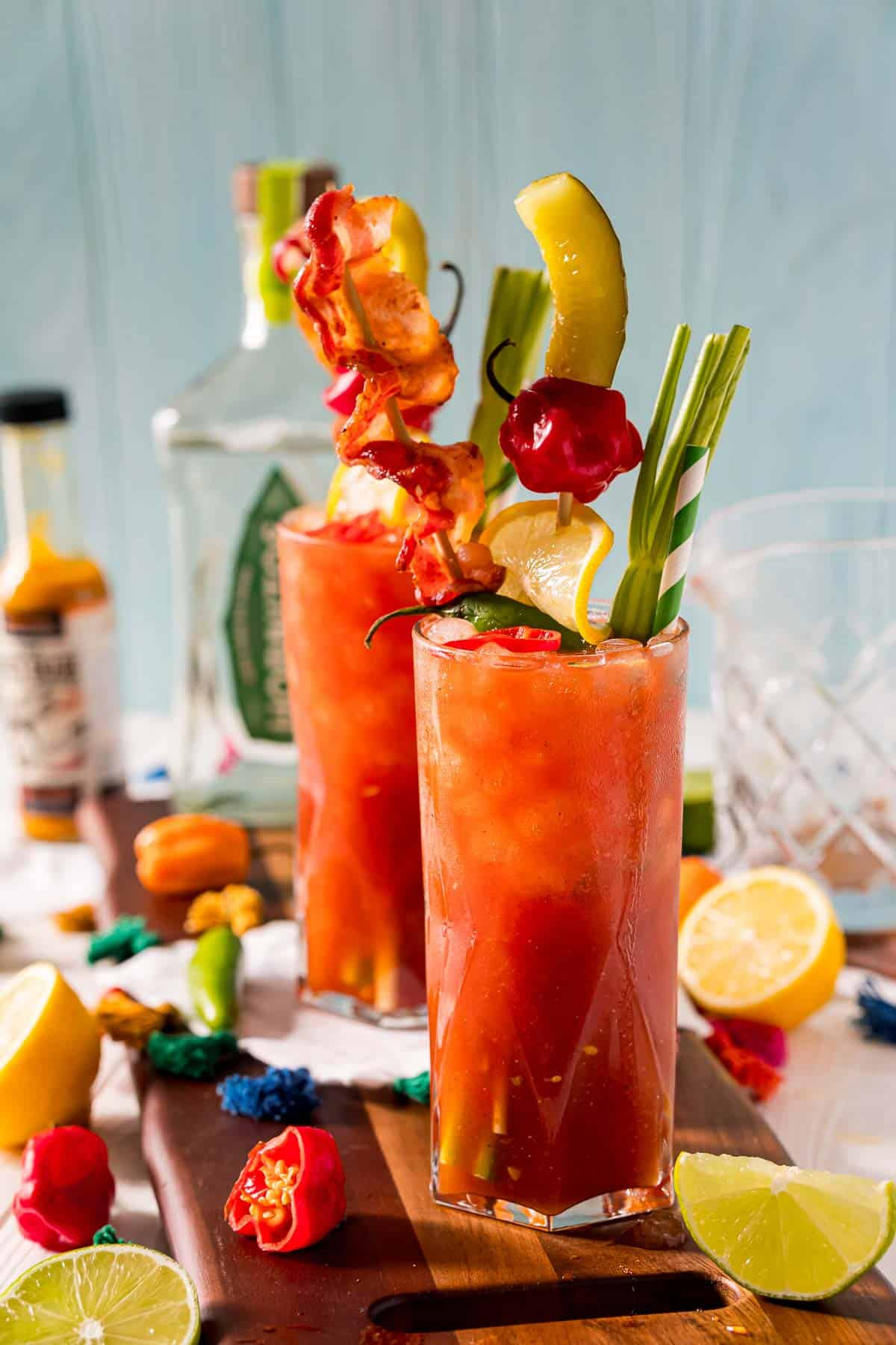 Two heavily-garnished tomato juice based cocktails in tall glasses.
