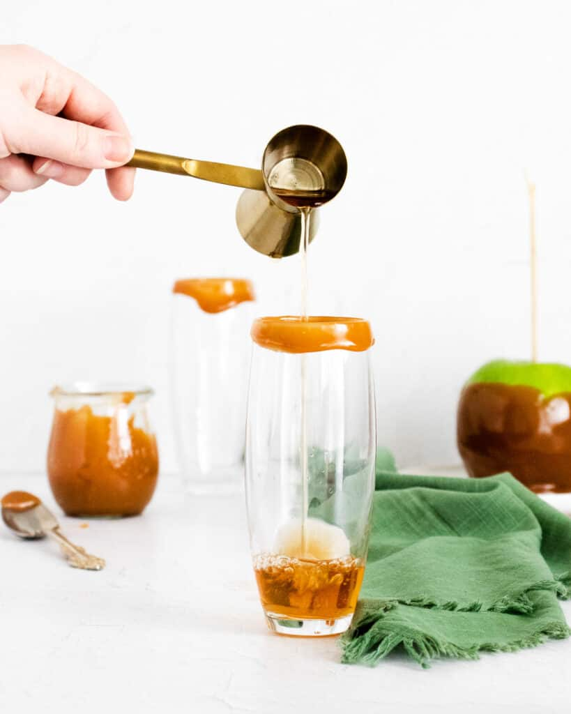 Apple cider being poured into a caramel-rimmed champagne flute.