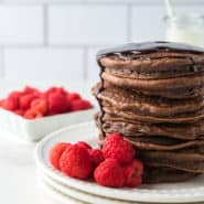 Large stack of chocolate pancakes on a plate with raspberries.
