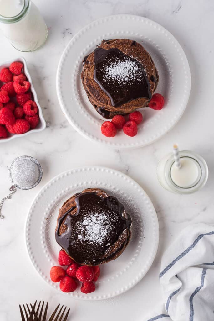 Overhead view of two plates of chocolate pancakes with chocolate syrup and raspberries.
