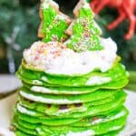 A high stack of bright green pancakes topped with whipped cream and frosted sugar cookies.