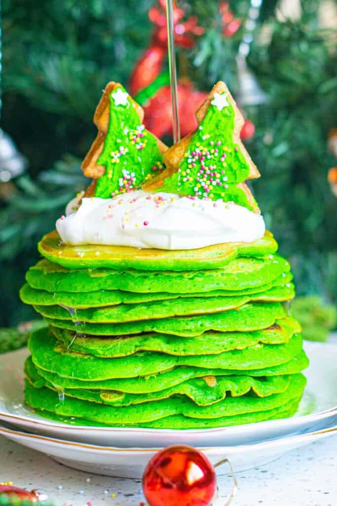 Tall stack of bright green Christmas pancakes with a Christmas tre in the background.