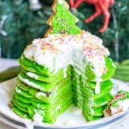 A stack of bright green pancakes with a wedge cut out to show texture. They are topped with whipped cream.