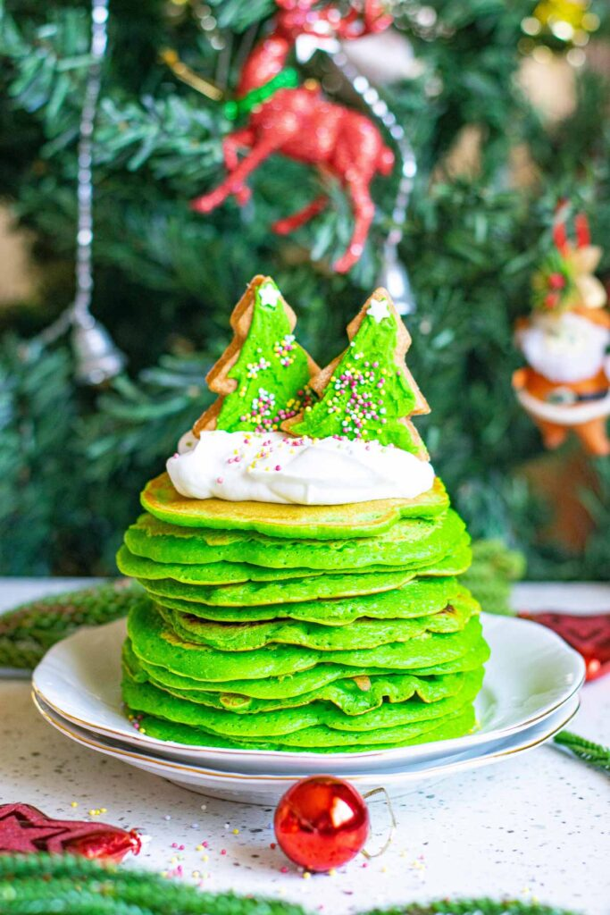 A stack of bright green pancakes topped with two Christmas tree shaped green cookies.
