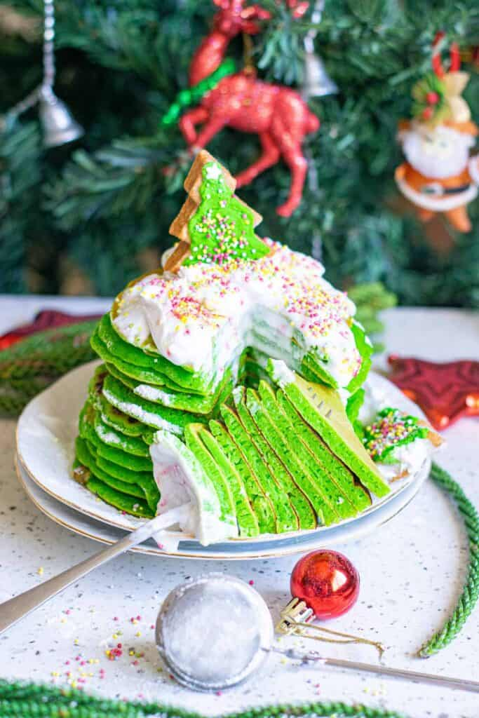 A wedge of green pancakes on a fork with the whole stack behind them.