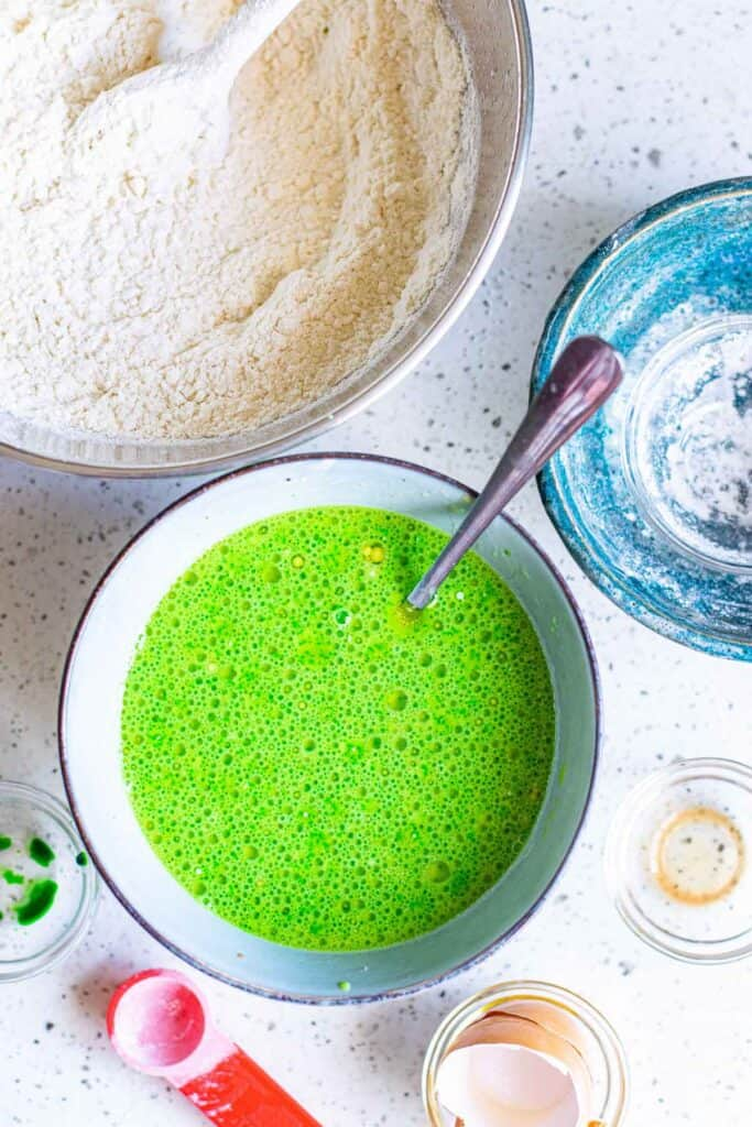 Wet ingredients for bright green pancakes in a mixing bowl.