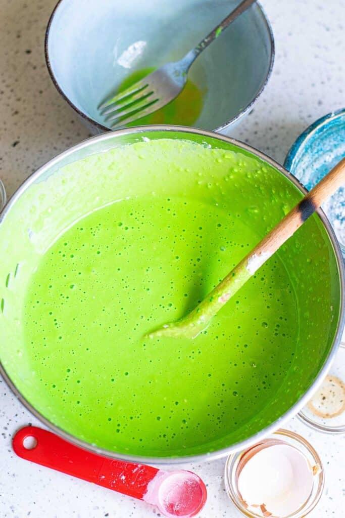 Bright green pancake batter in a mixing bowl.