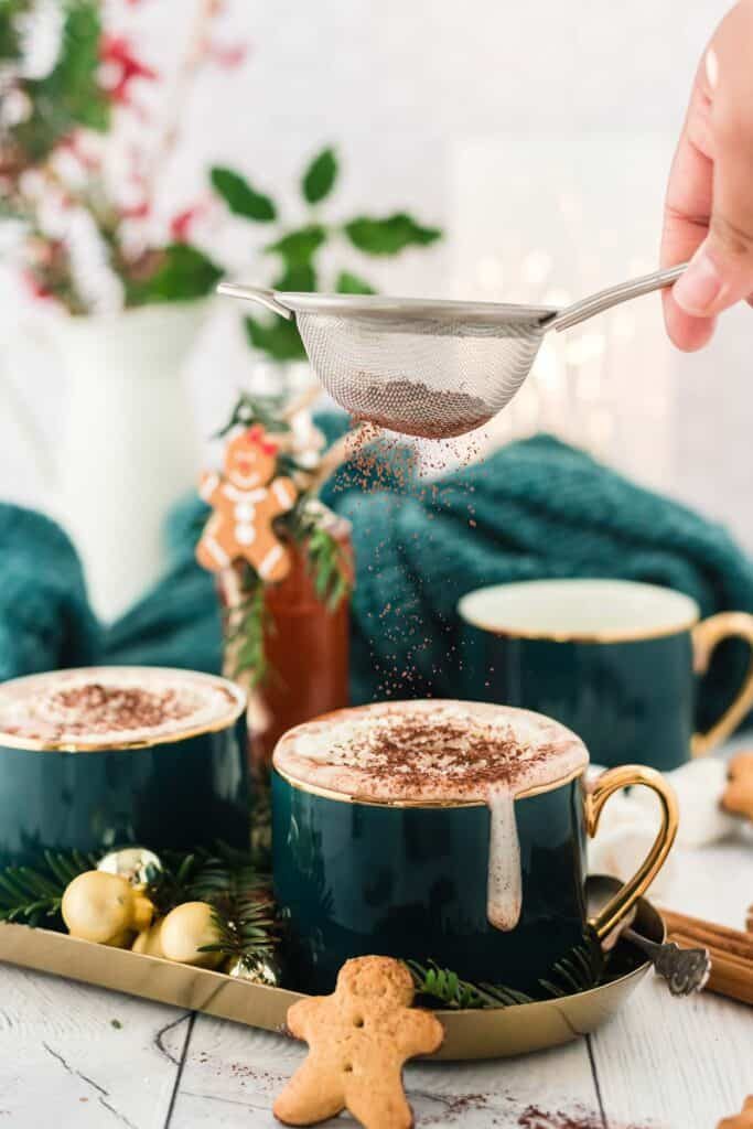Sprinkling cocoa on hot chocolate