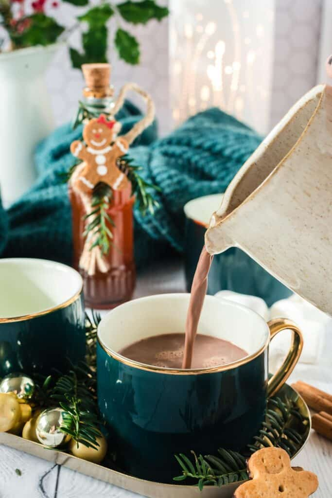 Cocoa being poured into a green mug.