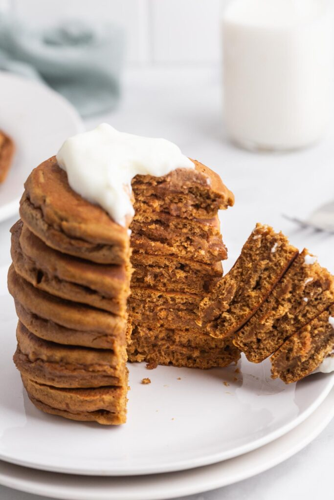A stack of brown pancakes with a wedge cut out to show texture.