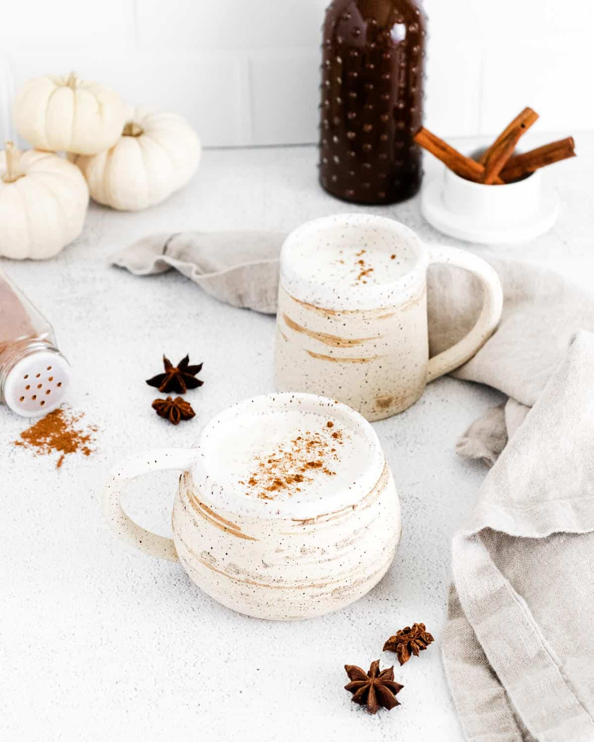 Pumpkin spice latte in white and earth tone mugs. Spices also pictured.