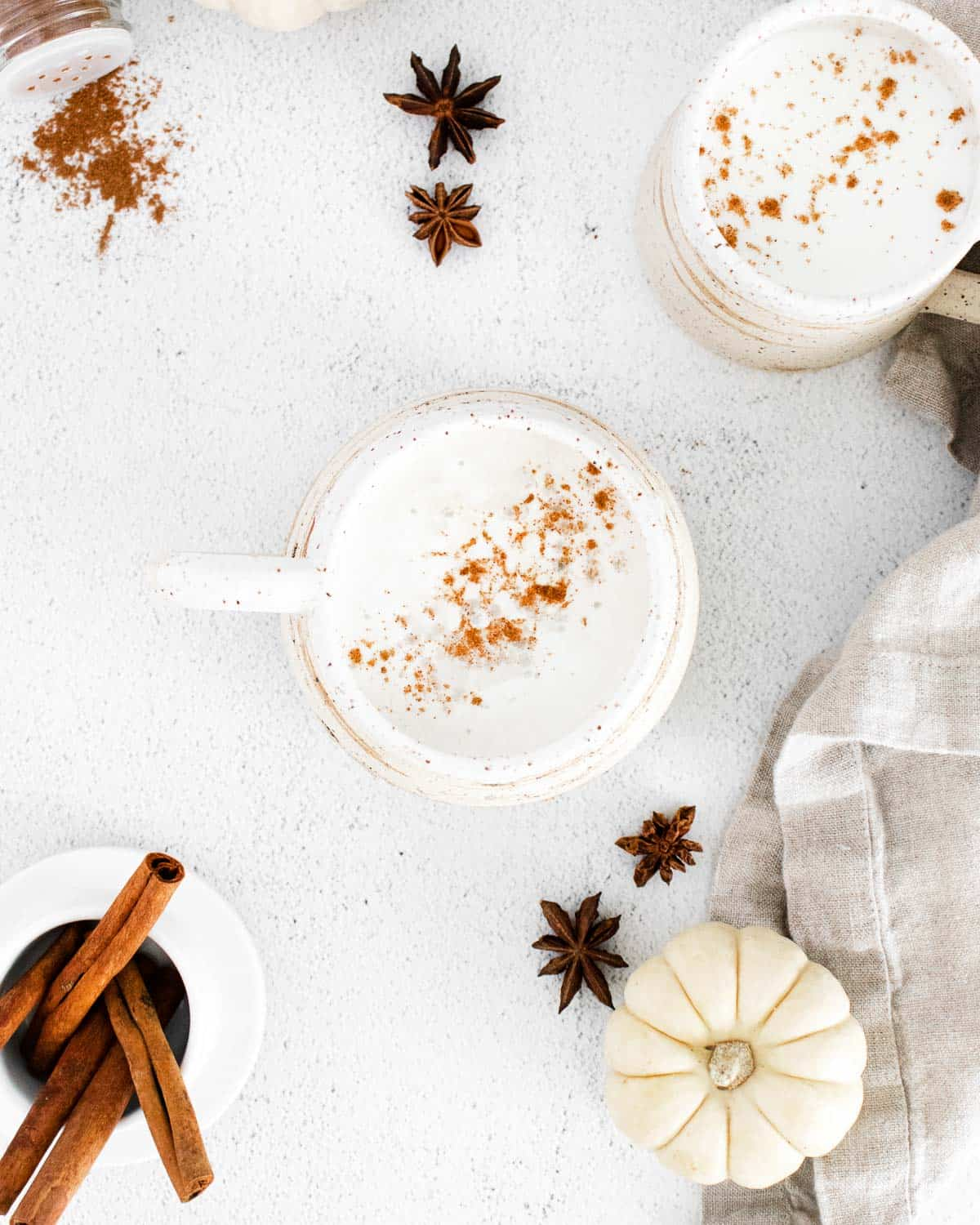 Overhead view of lattes, whole spices, and white pumpkins.