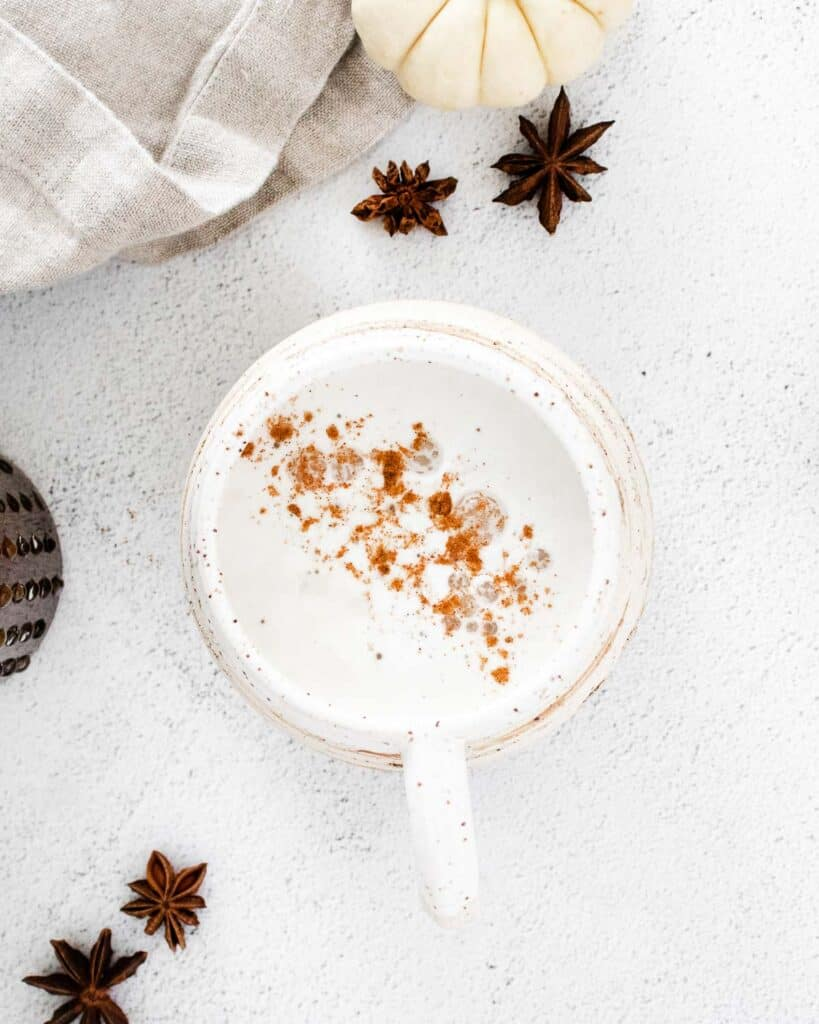 Overhead view of a latte sprinkled with pumpkin pie spice.