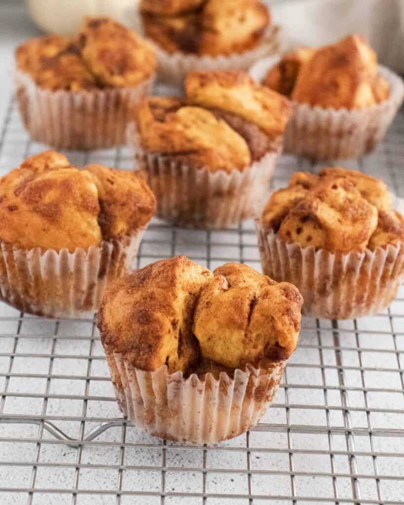 Muffins made from cinnamon rolls, on a cooling rack.