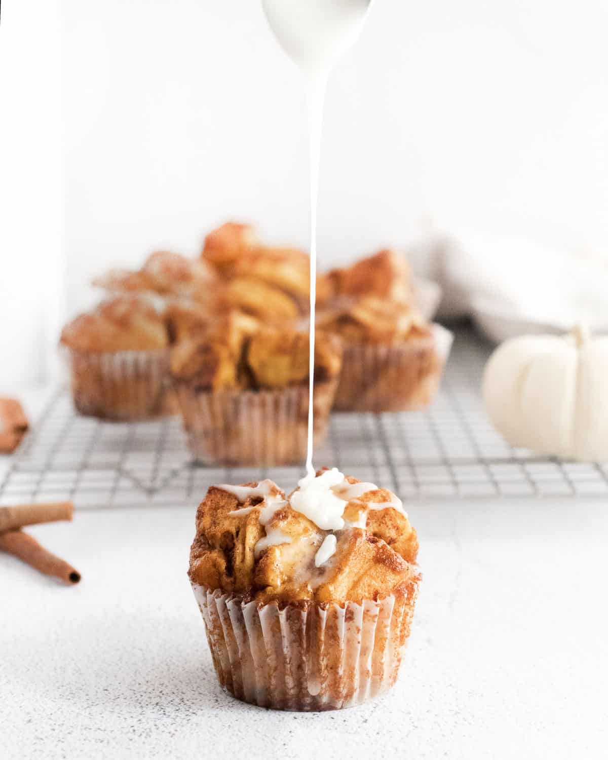 Pumpkin monkey bread muffin being drizzled with glaze.