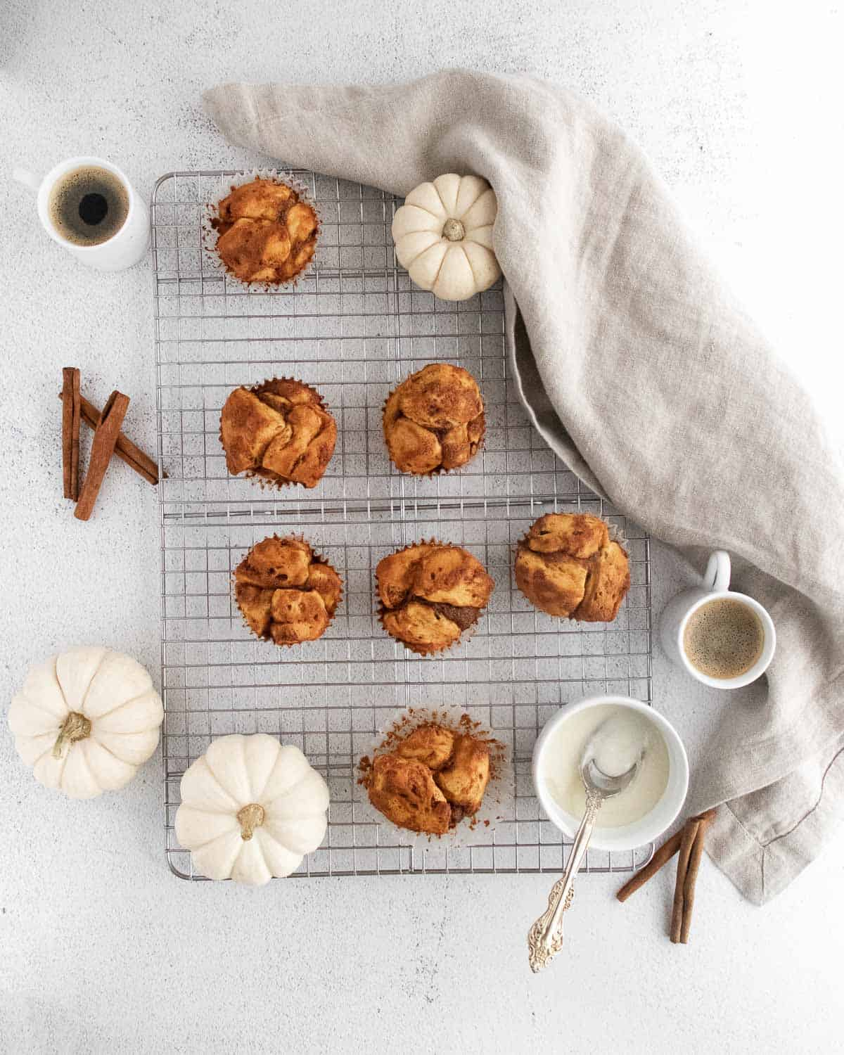 Overhead view of monkey bread muffins on a cooling rack, with white pumpkins and cinnamon sticks.