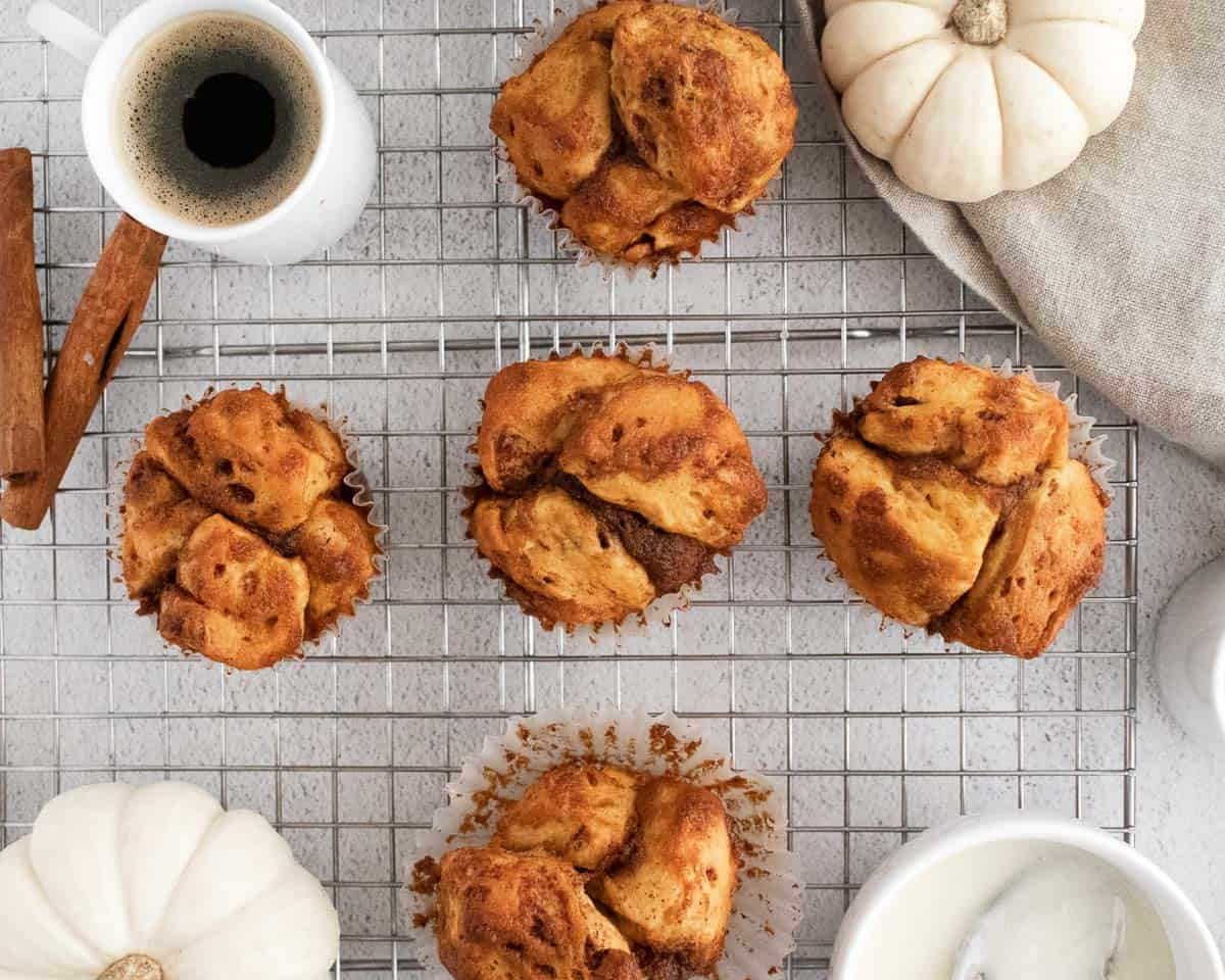 Overhead view of monkey bread muffins, white pumpkins, and coffee in white cups.