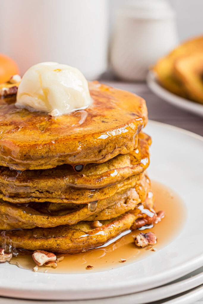 Stack of pumpkin pecan pancakes with butter and maple syrup.