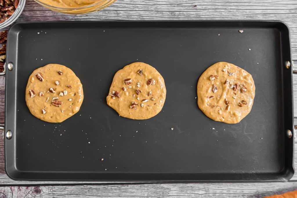 Half cooked pumpkin pecan pancakes on a black griddle.