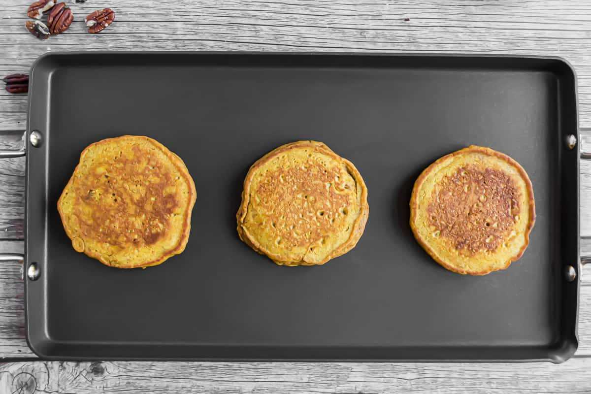 Three fully cooked pancakes on a black griddle.