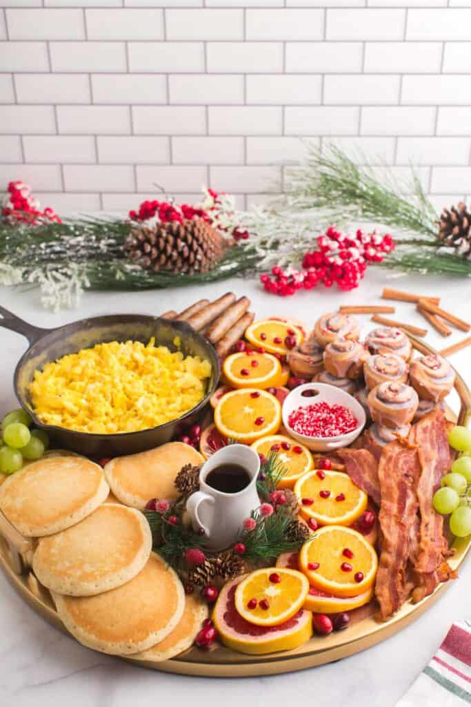 Festive Christmas brunch board with cinnamon rolls, pancakes, eggs, and more.