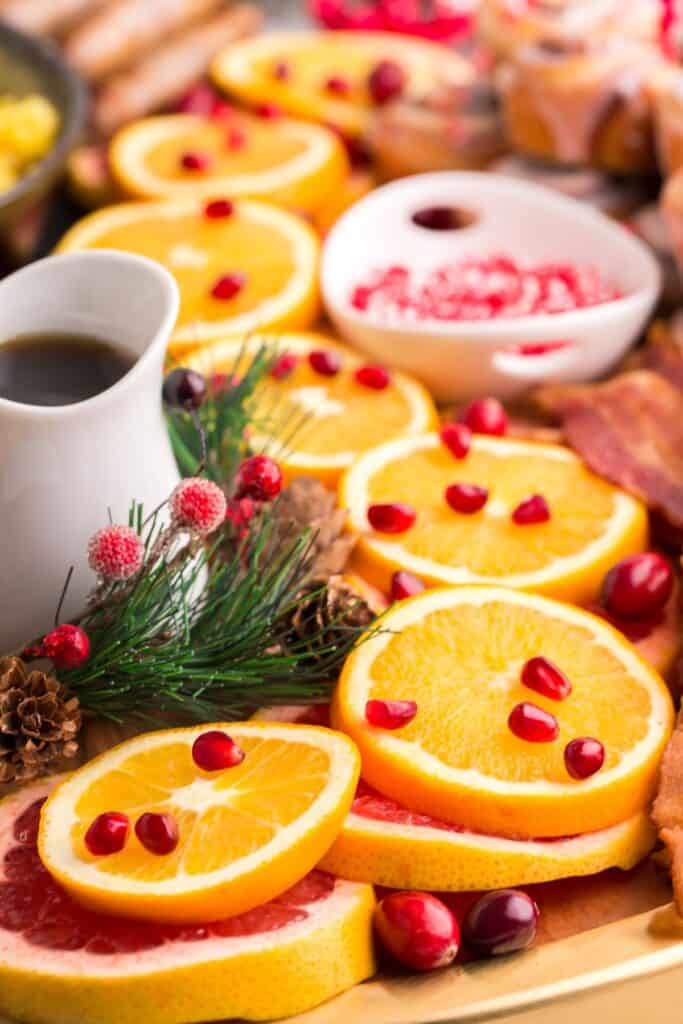 """Oranges and pomegranate seeds and syrup on a festive """"charcuterie"""" board."""